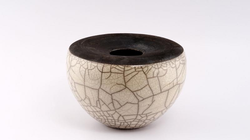 Voluminöses Rakugefäß mit kleine Öffnung. Die Glasur ist milchig weiß und weist ein gleichmäßiges Craquelé Rissnetz  auf.