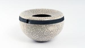 Voluminöses Rakugefäß mit kleine Öffnung und schwarzen Rand. Die Glasur ist milchig weiß und weist ein dichtes, gleichmäßiges Craquelé Rissnetz  auf.