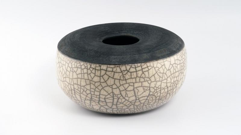 Creme weißes Rakugefäß mit großen Durchmesser und kleine Öffnung. Die Oberseite ist naturschwarz. Die Unterseite ist zur Gänze Glasiert